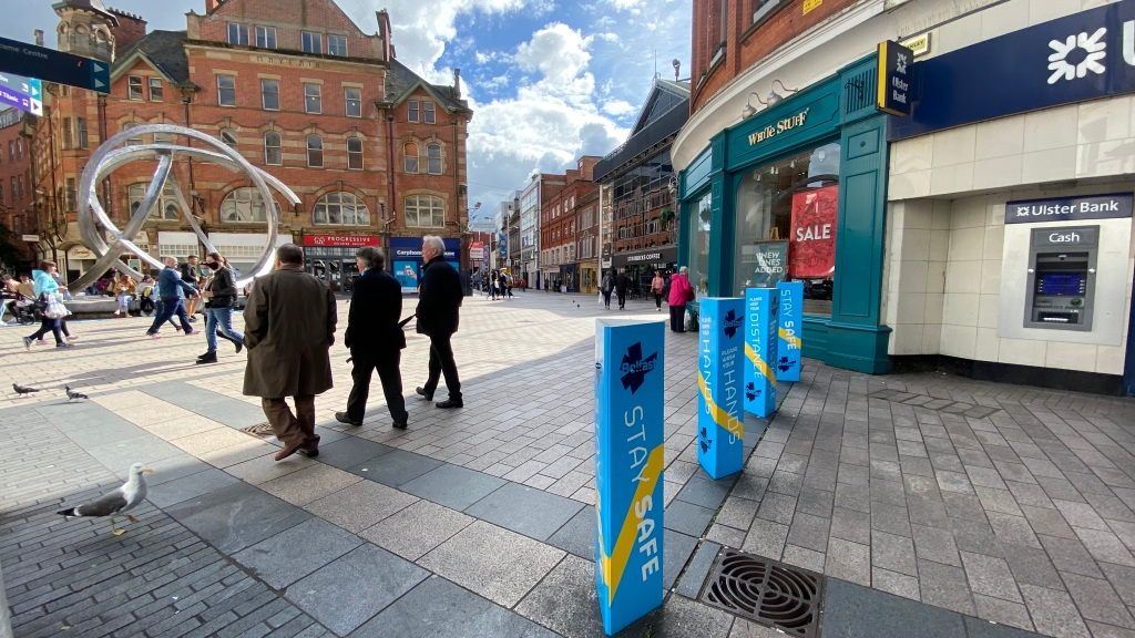 This is an image displaying citizens walking during exit-strategies of Northern Ireland in Arthur Square. There are Covid-19 signs and messages all around.