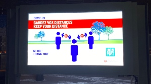 This is a photo of a poster informing to keep distance between people during the COVID-19 pandemic in the Old Port of Montreal, Canada.