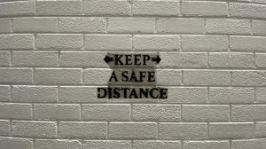 """Graffiti text of Covid-19 """"keep a safe distance"""" during Lockdown 3 in Belfast, Northern Ireland"""